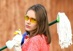 girl in glasses with a mop, ready for major cleaning